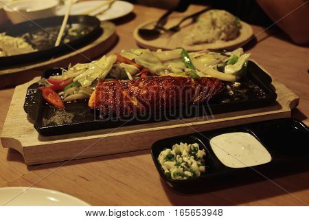 Salmon and vegetable hot pot on wooden table.