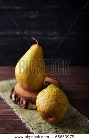 Two fresh green pears on a rustic background with napkin. Vertical shot