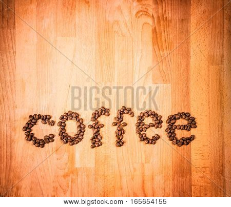 Coffee beans on wood background. Shape of word Coffee made from coffee beans, decorated with red heart on wooden surface. Roasted coffee beans on rustic wood background. Top view. Copy space.