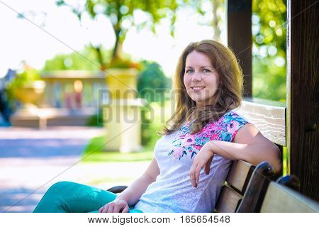 Portrait Of A Pretty Thoughtful Lady Sitting On  Banch In  Park With Artistic Colors And Shadows Add