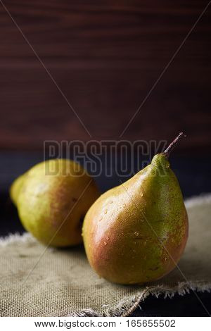 Fresh green pears on a rustic background on a napkin. Vertical shot