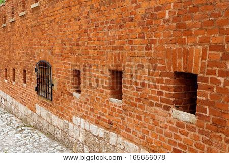 A strong red brick wall surrounding an ancient castle or antique fortress as fortification. The bricks and blocks have different color tones and shades of red. Square holes and a steel grid opening lead into the inner of the medieval structure.