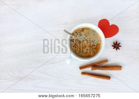 Black frothy espresso with cinnamon and heart symbol on a light wooden table top view / coffee with love