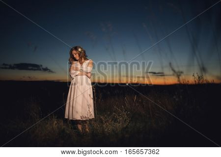 Beautiful bride in a dress on background of sunset. Blurred
