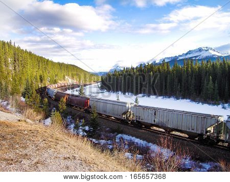 Freight Train Running along Bow River in Winter Canadian Rockies Alberta Canada