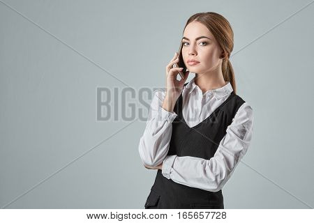 Young girl talking at the cellphone on a gray background. Woman looking at the camera