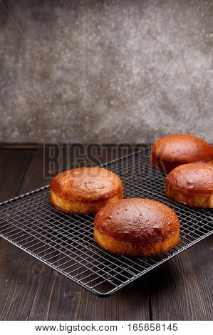 Tasty Fresh Newly-baked Buns On A Iron Grid Over Wooden Background