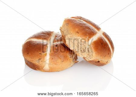 closeup of hot cross buns with raisins on white background