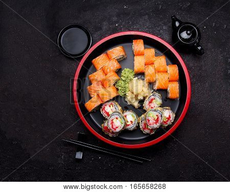 Japanese Cuisine. Sushi Roll With Fresh Ingredients On A Round Wooden Plate And Stone Background.