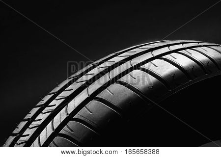 Studio shot of a summer, fuel efficient car tire on black background. Contrasty lighting and shallow depth of field