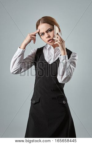 Young girl talking at the cellphone on a gray background. Emotions. Woman looking at the camera