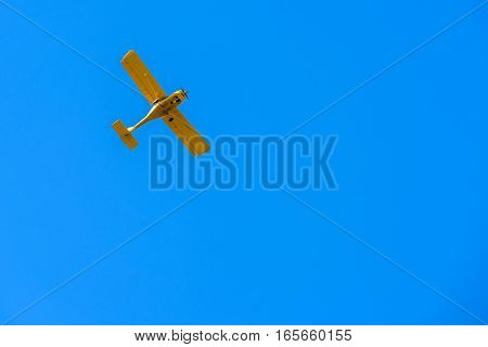 retro yellow colored biplane flying against blue sky.