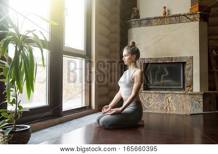 Young attractive woman practicing yoga, sitting in seiza exercise, vajrasana pose, working out, wearing sportswear, grey pants, bra, indoor full length, home interior background, near floor window