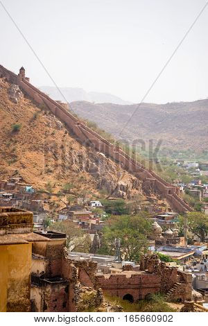 April 15 2016. Wide scenic landscape of the walls of the Amer Fort also known as the Amber Fort running along a mountain with a town in the valley below. Travel and landscape photography.