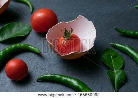 Fresh tomatoes in cracked eggshell on black stone background