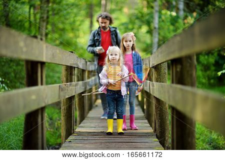Two Cute Little Sisters Hiking In A Forest With Their Grandmother