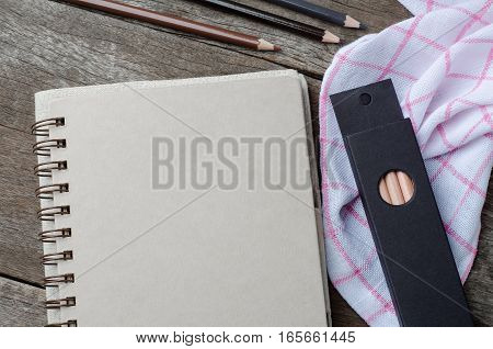 Blank paper diary with pencils on wooden background
