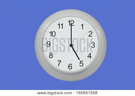 Wall watch showing five o'clock isolated on blue background