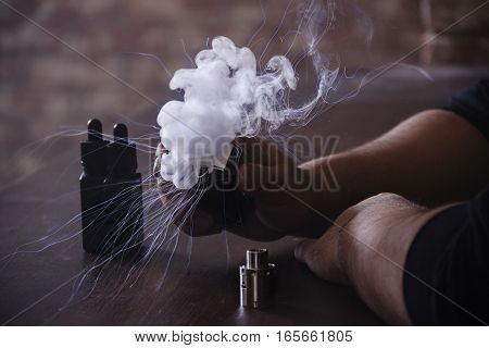 Vaping device in in the man's hand. Electronic cigarette, vape