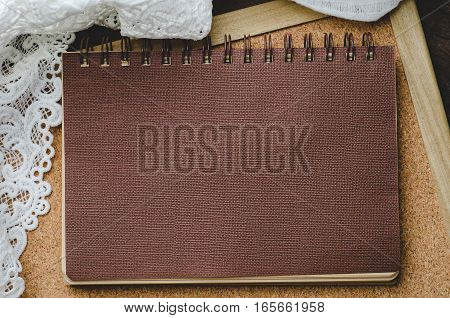 Brown paper diary with lace on corkboard and wooden background