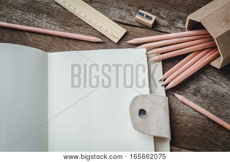 Blank daily planner notebook with pencils pencil sharpener and ruler on wooden background