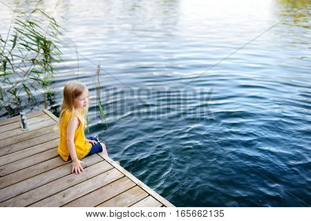 Cute Little Girl Sitting On A Wooden Platform By The River Or Lake