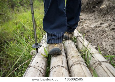 hiker's feet on bamboo bridge in Colombia