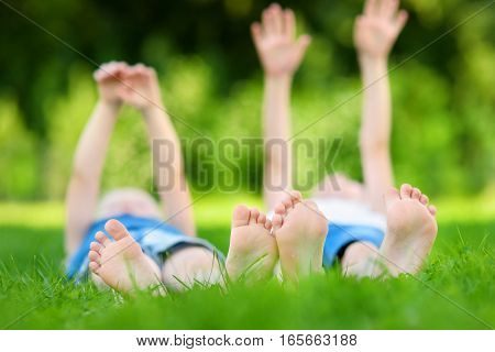 Two Childrens Feet On Grass Outdoors
