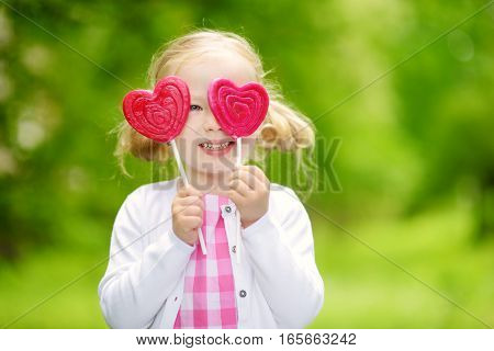 Cute Little Girl Eating Huge Heart-shaped Lollipop Outdoors On Beautiful Summer Day