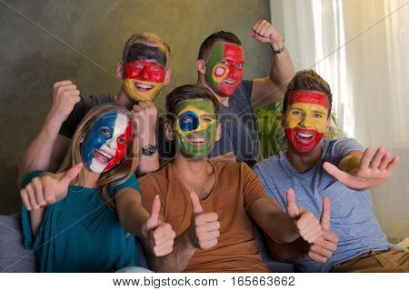 Happy soccer fans with colored faces cheering on their favourite team