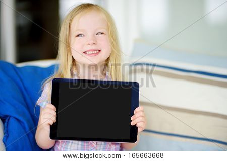 Smart Little Schoolgirl With Digital Tablet In At Home