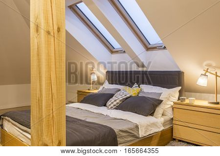 Marital bed at the attic with bedside cabinet