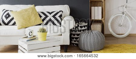 Cozy living room with white sofa pattern pillows DIY small table. pouffe and bike