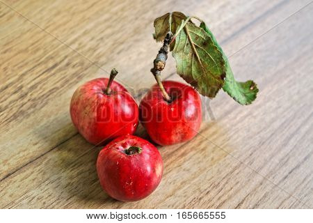 Closeup of tiny red apples on a wooden table