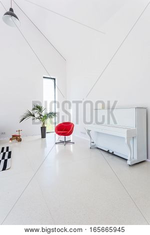 Image of white and spacious living room with modern red chair piano and decorative houseplant