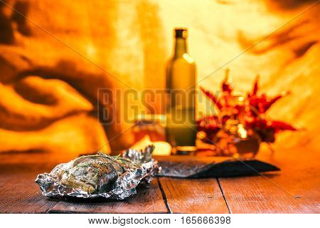 Whole fish baked on foil over fire light background