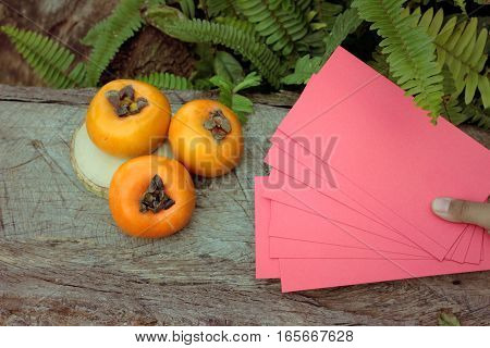 persimmons fruit with red envelopes Chinese New Year