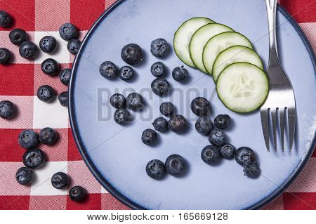 Close up overview of fruit and veggie on a blue plate.