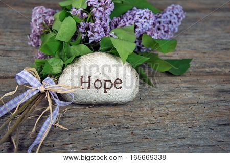 word hope carved in stone with lilac bouquet and gingham bow on rustic barn wood
