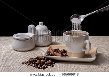 Sugar being poured into coffee that is next to coffee beans and cinnamon sticks.
