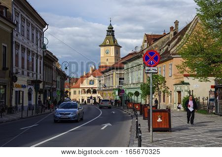 Brasov, Romania - April 29, 2014: Street of old town with town hall building on Council Square at background.