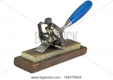 Studio shot of chisel clamped in angle guide jig resting on grinding whetstones on white background poster