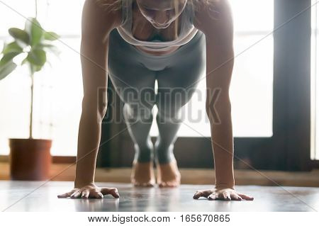 Young attractive woman practicing yoga, standing in Push ups, press ups, phalankasana exercise, Plank pose, working out, wearing sportswear, grey pants, bra, indoor, home interior background. Close up