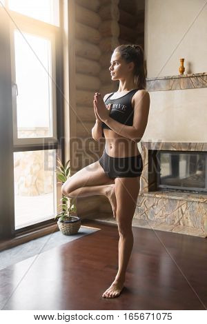 Young attractive woman practicing yoga, standing in Tree exercise, Vrksasana pose, working out, wearing sportswear, black tank top, shorts, indoor full length, home interior background, near fireplace