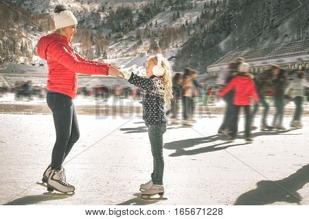 Happy family outdoor ice skating at rink. Mother and daughter has winter activities. Mom, kids. Medeo stadium. Almaty. poster