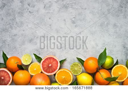Different citrus fruit on grey concrete table. Fruit food background. Healthy eating and diet.
