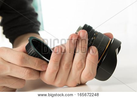 Zoung photographer checking dslr fisheye camera lens