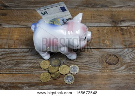 Pile of euro coins and a piggy bank on an old wood