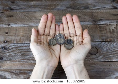 Several euro coins on the hands of a woman on an old wood