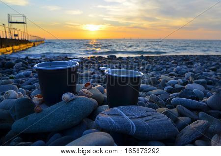 two cups of coffee on the sea coast. beach. backgrounds for advertising and travel vouchers. For hikers freelancers. sea and beach advertising. Rest for two love honeymoon.